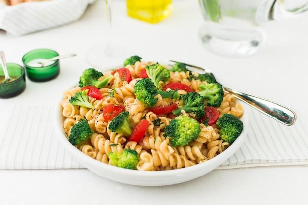 A prepared dish of fusilli with tomato and broccoli