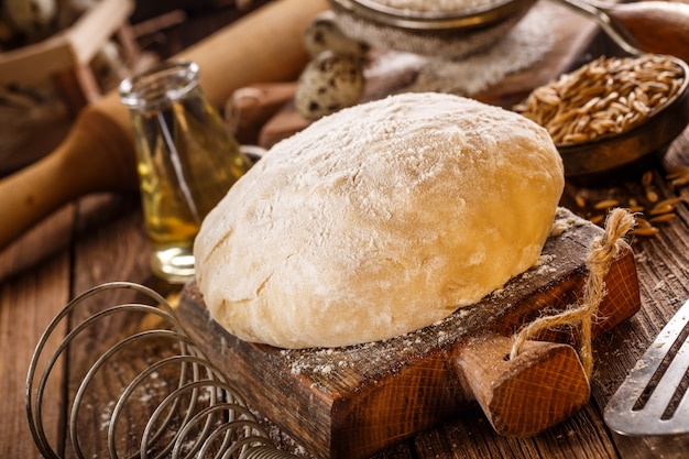 Prepared dough on wooden board. selective focus.