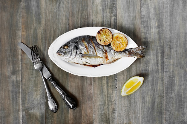 Prepared fish on the white plate, on the old wooden table