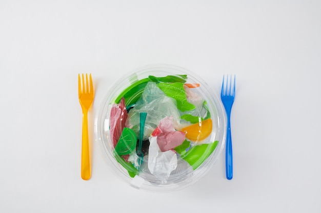 Prepared fork nearby. transparent package with trash and plastic bags inside as literal meal for our environment