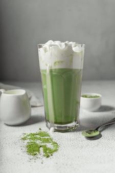 Приготовленный чай матча в прозрачном стакане. восхитительный напиток из порошка японского зеленого чая. вертикальная позиция