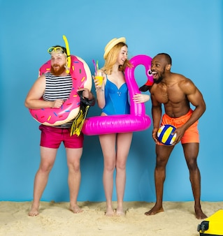 Prepared for travel. happy young friends resting and look astonished on blue studio background. concept of human emotions, facial expression, summer holidays or weekend. chill, summertime, sea, ocean.