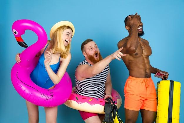 Preparato per il viaggio. happy giovani amici in appoggio e puntando su sfondo blu studio. concetto di emozioni umane, espressione facciale, vacanze estive o fine settimana. freddo, estate, mare, oceano.