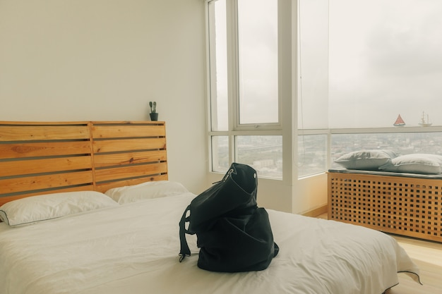 寝室での旅行のために黒いバックパックを準備しています。