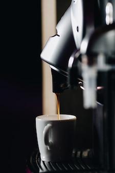 어두운 그림자 배경에 흰색 컵에 쏟아지는 음료의 측면보기와 함께 커피 머신을 사용하여 강력하고 갓 내린 에스프레소 커피 한 잔을 준비합니다. 고품질 사진