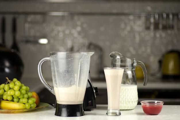 부엌에서 과일과 함께 우유 칵테일 준비하기