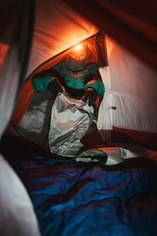 寒い夜のためにテントで寝袋を準備する