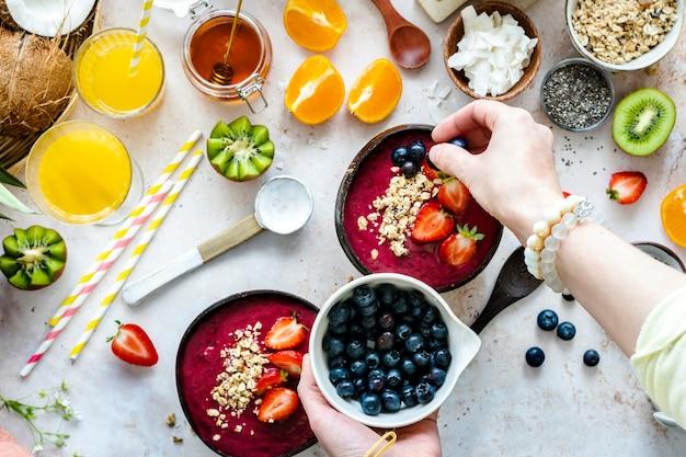 Preparare una ciotola di acai in stile piatto con frutti tropicali e cereali