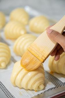焼きクロワッサンの準備と卵でのブラッシング。
