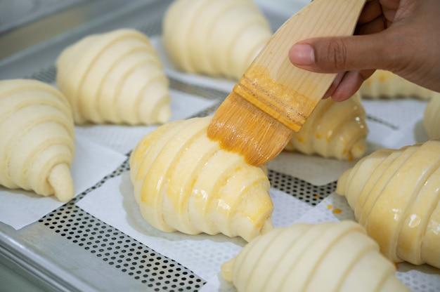 Приготовление выпекание круассанов, смачивание яичного мыла на сырых круассанах, тесто на противне.