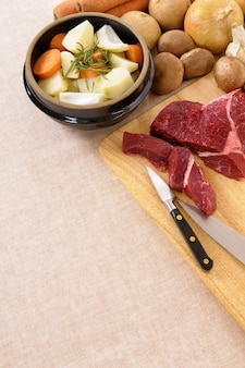 Preparing beef for casserole or stew with ingredients and knife on kitchen chopping board.