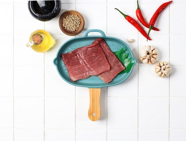 キッチンで牛肉を準備し、唐辛子、ニンニク、スパイスをのせます。エンパルデージングを行う準備。白い背景にスペースをコピーする