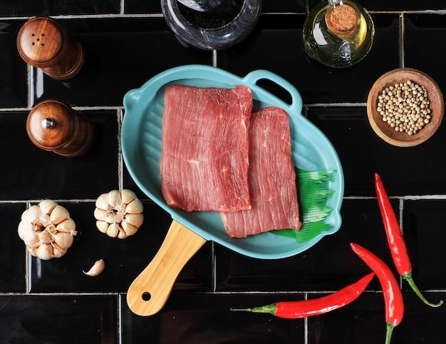 キッチンで牛肉を準備し、唐辛子、ニンニク、スパイスをのせます。エンパルデージングを行う準備