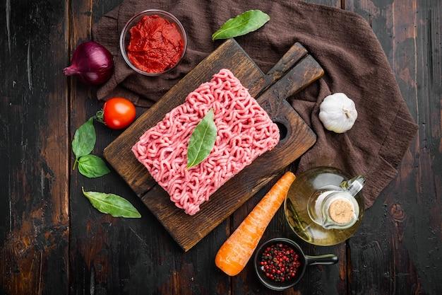 오래 된 어두운 나무 테이블에 나무 커팅 보드에 볼로냐 소스 재료, 다진 고기, 토마토, 허브 세트 준비