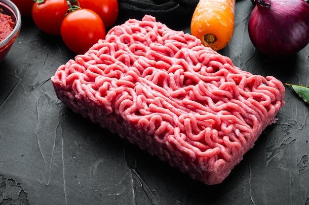검은 돌 배경에 볼로네제 소스 재료, 다진 고기, 토마토, 허브 세트 준비
