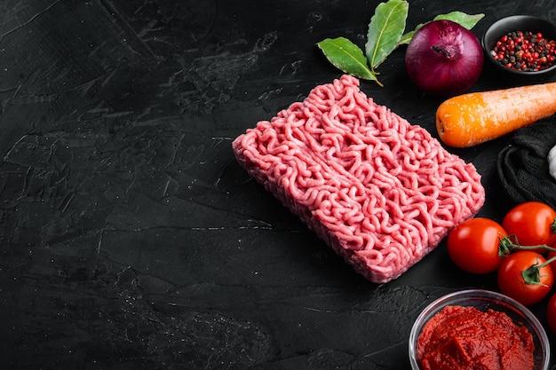 ボロネーゼソースの材料、ひき肉、トマト、ハーブセットを黒い石のテーブルで準備する