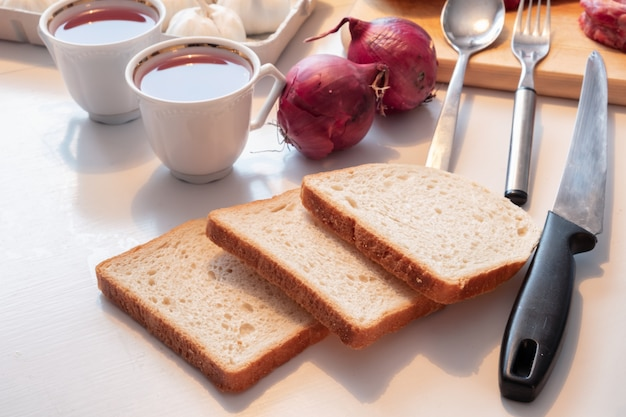 Preparing bread with tea cup and kitchenware, egetable and meat on table