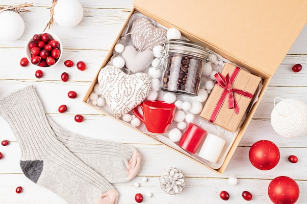 Готовим посылку, сезонную подарочную коробку с кофе, свечами и шерстяными носками. персонализированная экологически чистая корзина для семьи и друзей на рождество. вид сверху, плоская планировка