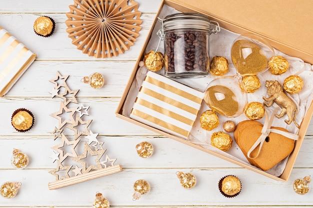 케어 패키지 준비, 커피, 쿠키 및 초콜릿이 담긴 계절 선물 상자. 황금 색상의 크리스마스 가족과 친구를위한 맞춤형 친환경 바구니.
