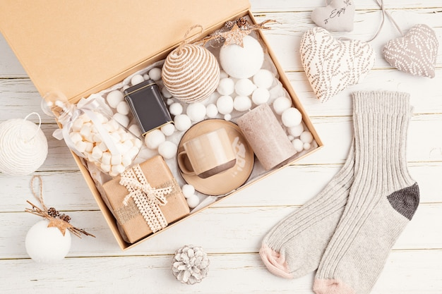 Preparing care package, seasonal gift box with tea, candle, cup and woolen socks. personalized eco friendly basket for family and friends for christmas. top view, flat lay