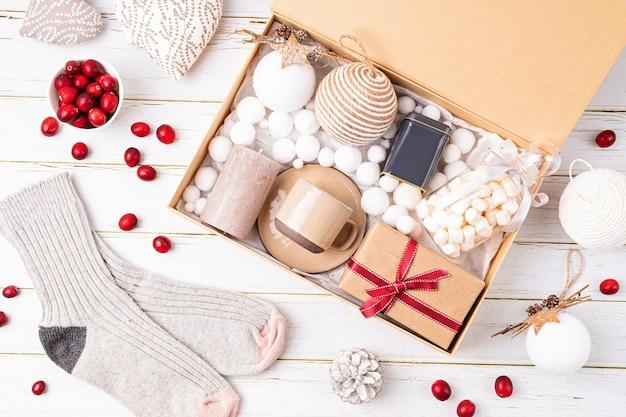 Готовим пакет услуг, сезонную подарочную коробку с чаем, свечами и шерстяными носками. персонализированная экологически чистая корзина для семьи и друзей на рождество. вид сверху, плоская планировка