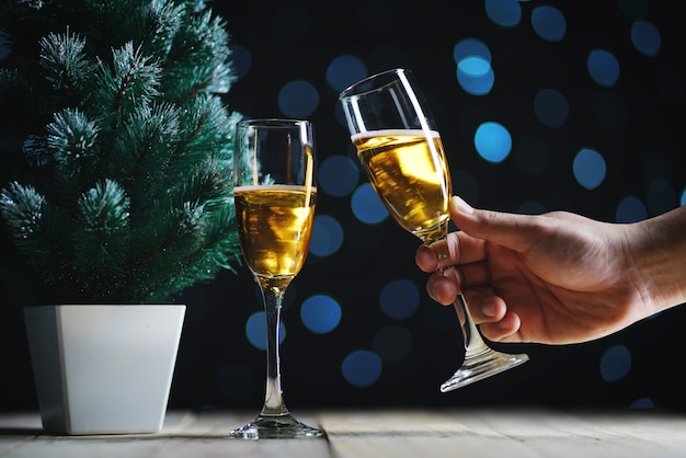 Preparing champagne besides small christmas tree dark glow lights background