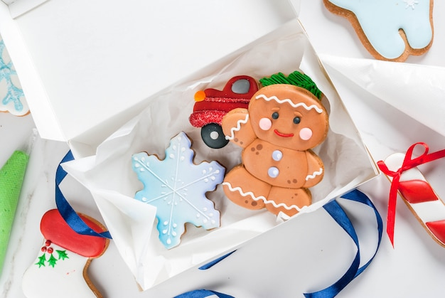 Preparing for christmas, decorating traditional gingerbread with multicolored sugar glaze, cookies, gingerbread in a white gift box, with ribbon bow, on a white marble table top  view copyspace