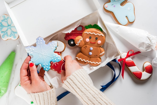 Preparing for christmas, decorating traditional gingerbread with multicolored sugar glaze, the girl folds the cookies in a white gift box, with ribbon bow, on a white marble table copyspace top view