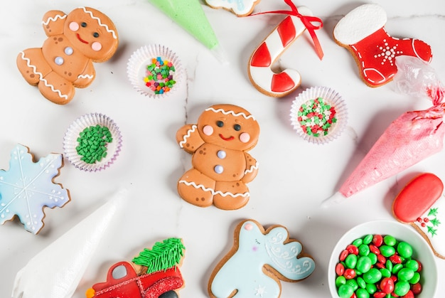 Preparing for christmas, decorating traditional gingerbread with multicolored sugar icing, biscuits, glaze in packages on a white marble table. top view
