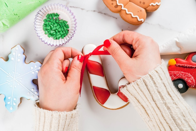 Preparing for christmas, decorating traditional gingerbread with multicolored sugar icing, white marble table. girl hands in picture knot ribbon bow on candy cane gingerbread, top view