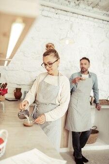 コーヒーの準備。一杯のコーヒーに蒸しミルクを注ぐ美しいバリスタの笑顔。