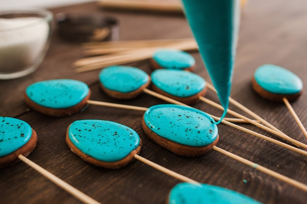 Preparing cookies with blue icing for decoration on rustic wooden table closeup
