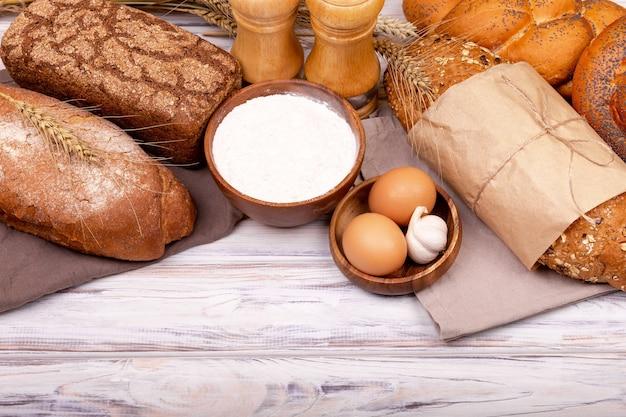 ベーキングのための生地の準備。自家製パンの作り方。パンの準備のための有機成分。小麦粉と白いテーブルの上に新鮮な生地。家庭用パン焼き面。フラットレイ、テキスト用のスペース