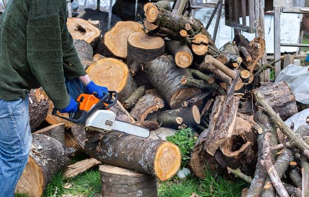 Заготовка дров на зиму, вишневые поленья навалены во дворе, крестьянин пил бензопилой