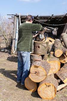 Заготовляя дрова на зиму, во дворе свалены в кучу вишневые поленья, фермер готовит бензопилу к работе