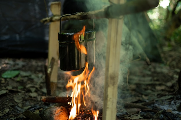 Preparing food on campfire, cooking in forest.