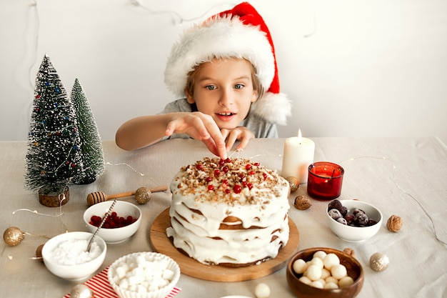 クリスマスディナーの食事の準備赤いサンタの帽子をかぶった男の子がクリスマスケーキを盗もうとしています