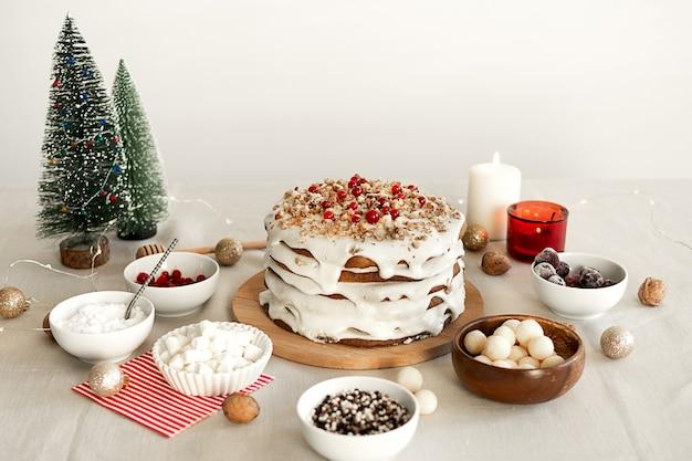 クリスマスディナーの食事の準備白いアイシングシュガーナッツと赤いクランベリーを使った自家製ケーキ