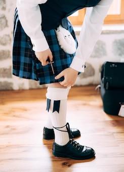 ハイソックスのスポーランと長い靴ひもが付いた靴でスコットランドの結婚式の男性の準備をする