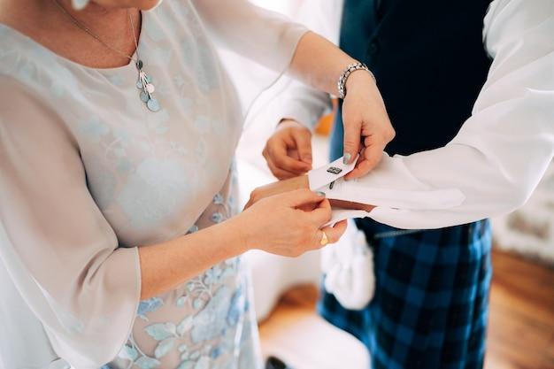 キルトの男のシャツにカフスボタンを留めるスコットランドの結婚式の女性の準備