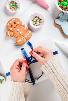 Готовясь к рождеству, украсив традиционные пряники разноцветной сахарной глазурью, девушка складывает печенье в белую подарочную коробку, с бантиком из ленты, на белом мраморном столе, вид сверху copyspace