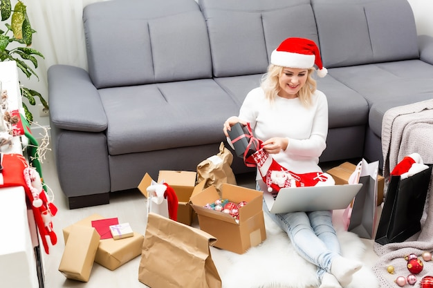 크리스마스 파티를 준비합니다. 노트북으로 선물과 장식을 주문하는 여성, 선물 상자와 패키지 사이에 앉아 공간 복사