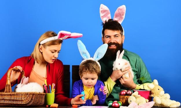 Готовимся к пасхе. счастливая семья в уши кролика, крася яйца дома.