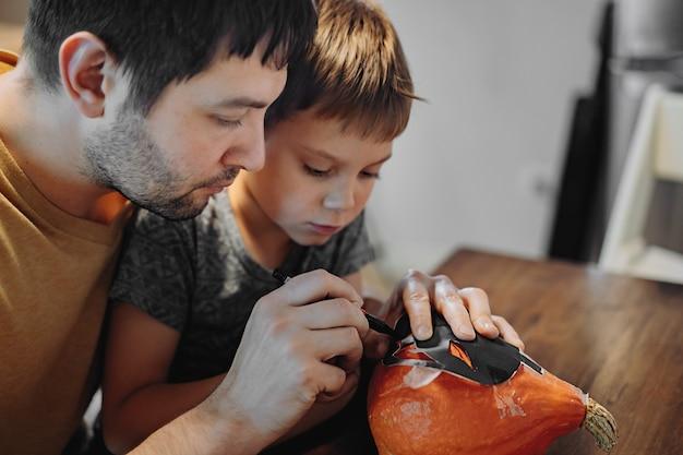 Подготовка к празднованию хэллоуина. кавказский мужчина со своим милым 6-летним сыном тянет глаза на тыкву, чтобы сделать традиционный фонарь джека. изображение с выборочным фокусом. фото высокого качества