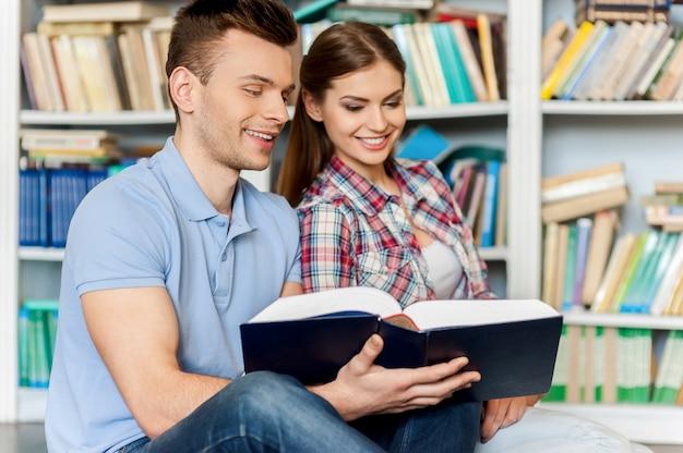 一緒に最終試験の準備。床に座って、図書館の本棚に対して一緒に本を読んでいる美しい若いカップル
