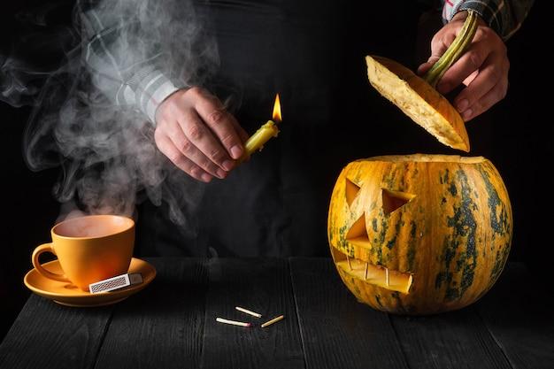 休日の準備-カボチャのクローズアップから切り取られたハロウィーンのランタン。人のろうそくを燃やすのは手です