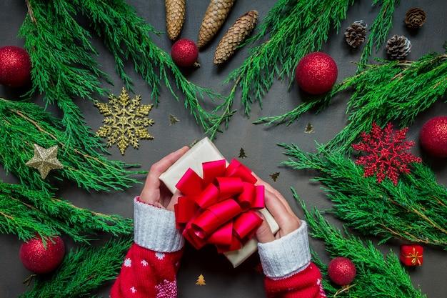休日の準備、手にプレゼントを包み、様々なクリスマスアクセサリー