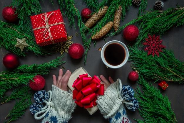 休日の準備、手にプレゼントを包んでクリスマスアクセサリーキャンドルツリー
