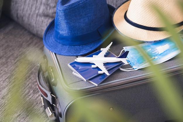 パンデミックでの旅行の準備。パスポート、帽子、フェイスマスク、手指消毒剤。コロナウイルスのパンデミック時の飛行規則。