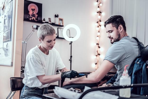 仕事の準備。並外れた短髪のタトゥーマスターがクライアントの手から髪を剃り、滑らかにします